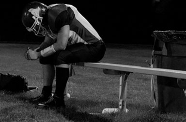 High school football player on bench